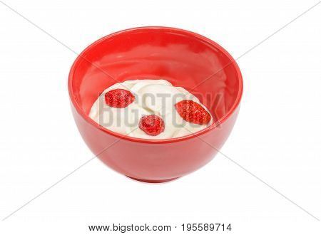 Fresh berries of the strawberry with whipped cream in red ceramic bowl on a light background