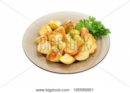 Serving of the country style fried potatoes sprinkled by chopped dill and twig of parsley on dark glass dish on a light background