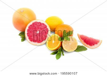 Appetizing juicy summer fruits isolated over the white background. Many colorful oranges, grapefruits, lemons and green mint herbs. Tropical citruses for meals and decoration.