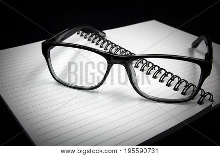 Notebook and glasses isolated on black background.