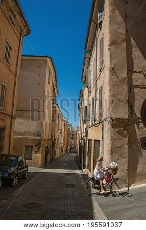 Aix-en-Provence, France - July 09, 2016. Woman riding bike in alleys of Aix-en-Provence, a pleasant and lively town in the French countryside. Provence region, southeastern France
