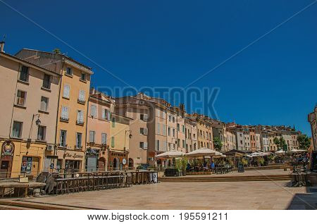 Aix-en-Provence, France - July 09, 2016. Square with colorful buildings and restaurant umbrella in Aix-en-Provence, a lively town in the French countryside. Provence region, southeastern France