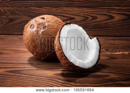 A close-up coconut on a saturated brown background. Nutritious coconuts laying on a dark wooden table. Delicious sweet hawaiian nuts cracked in half.