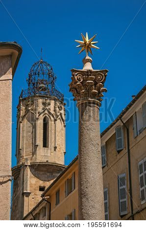 Column with golden star on top and bell tower in Aix-en-Provence, a pleasant and vivid city in the French countryside. Located in the Bouches-du-Rhone department, Provence region, southeastern France