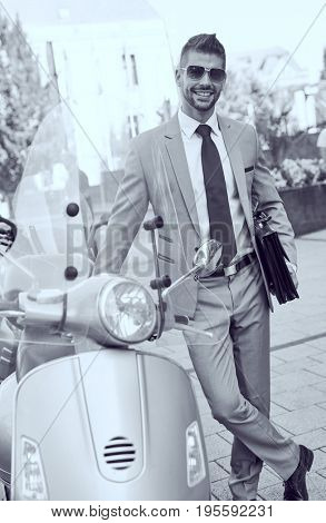 Successful dedicated young businessman on street wearing suit tie and sunglasses leaning against a moped.