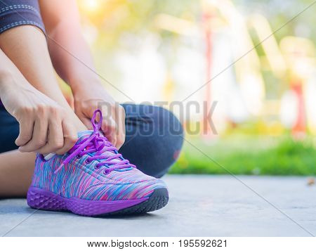 Running shoes - closeup of woman tying shoe laces. Female sport fitness runner getting ready for jogging with fitness equipments in backgroound