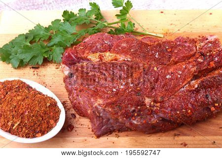 Raw beef steak with spices Leaves of coriander on wooden cutting board. Ready for cooking