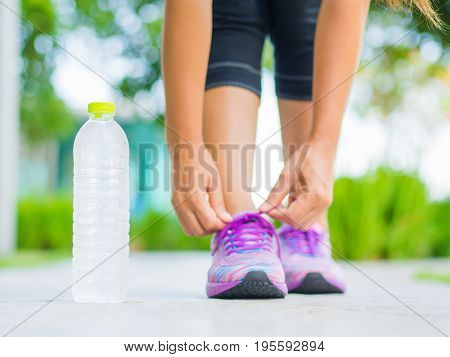 Running shoes - closeup of woman tying shoe laces. Female sport fitness runner getting ready for jogging with water bottle in garden backgroound