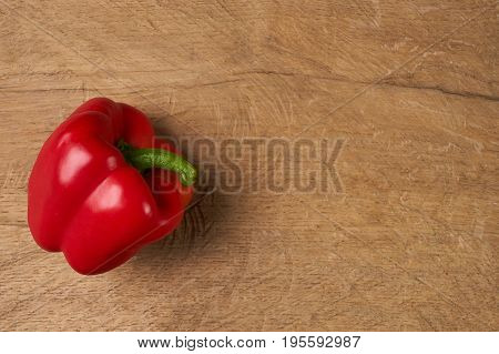 Sweet bulgarian red bell pepper on wooden background. Top view copy space.