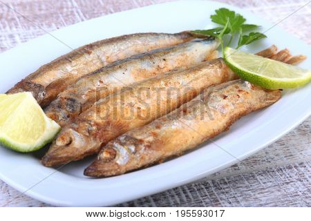 Deep frying small fish capelin and sliced lemon on white plate. Good snack to beer