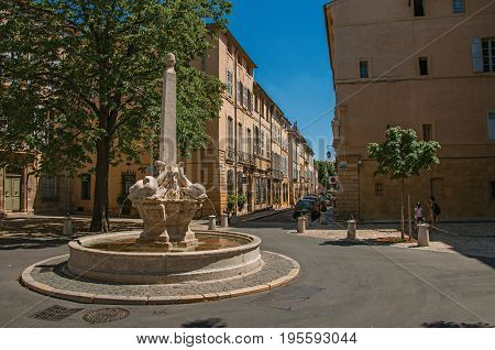 Aix-en-Provence, France - July 09, 2016. Street with buildings and fountain in sunny afternoon in Aix-en-Provence, a pleasant and lively town in the countryside. Provence region, southeastern France