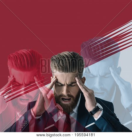 Stressed young bearded businessman suffering from headache