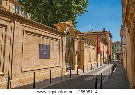 Aix-en-Provence, France - July 09, 2016. Alley with buildings and gate in Aix-en-Provence, a pleasant and lively town in the French countryside. Provence region, southeastern France