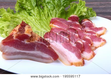 Fresh homemade smoked bacon with leaves lettuce on white plate. Selective focus