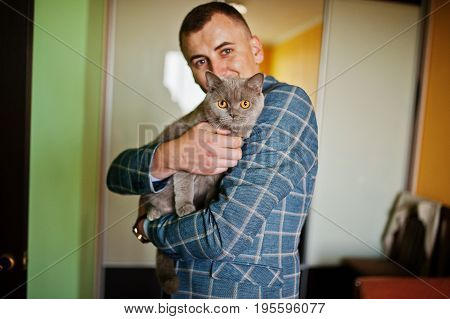 Handsome Groom Posing With A Little Cute Kitten In His Room.