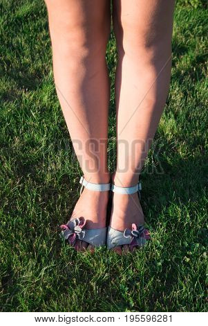 Beautiful legs of a girl in blue sandals on a green lawn
