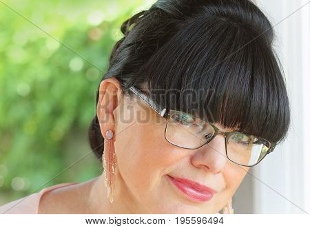 Close up portrait of elegant middle aged woman with brown hair, red lips and fresh makeup - beauty concept .