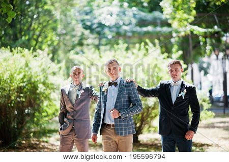 Handsome Groom With His Groomsmen Walking In The Park Next To The Lake.