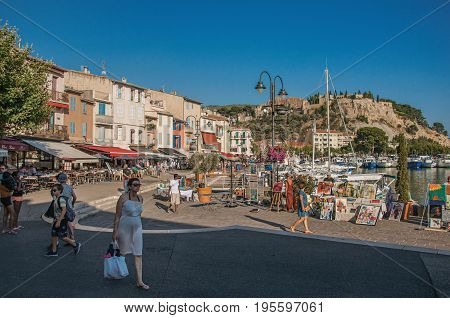 Cassis, France - July 09, 2016. View of boats, yachts and people in the city center of Cassis, a beautiful and sunny seaside town with harbor. Provence region, southeastern France