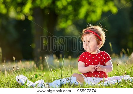 Baby girl in red summer dress sitting on the grass.