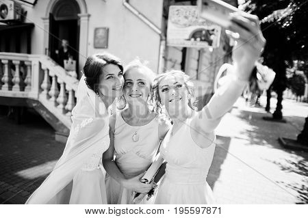 Bride With Bridesmaids Taking A Selfie On City Streets. Black And White Photo.