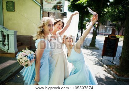 Bride With Bridesmaids Taking A Selfie On City Streets.