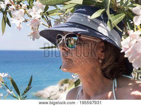 Greece. The island of Zakynthos, the Ionian Sea. Woman with a reflection in glasses of a kind on blue caves