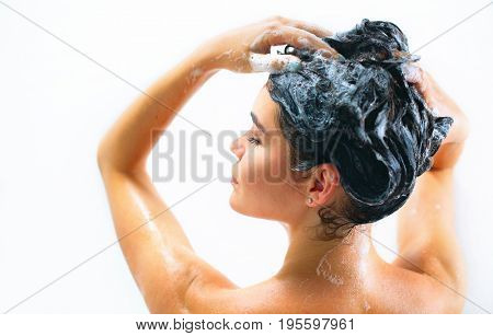 Washing hair. Beautiful naked young woman is smiling and using shampoo while taking shower in bathroom. beauty sexy model girl washing her long black hair. Isolated on white background