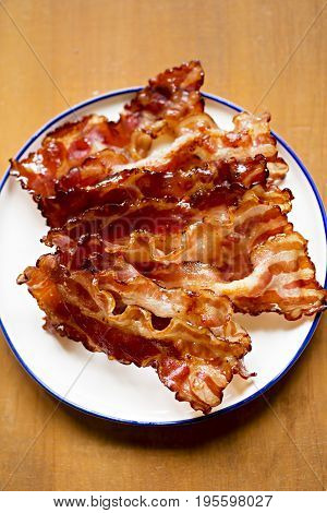 Streaky fried bacon rashers for breakfast on wooden table