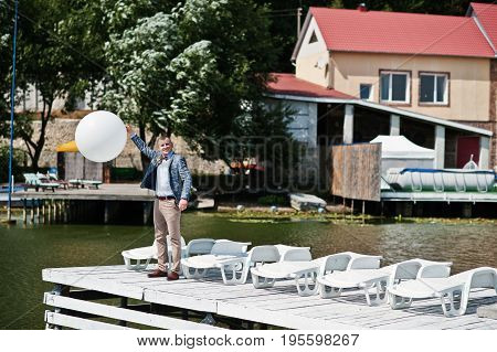 Handsome Lonely Groom Holding A White Balloon On A Wharf On His Wedding Day.