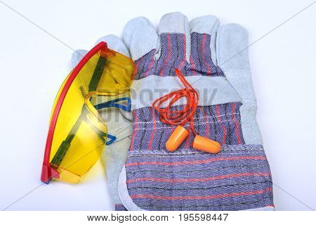 Orange earplug, safety glasses and gloves for work. Earplug to reduce noise on a white background