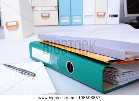 Folder file, note and pen on the desk. blurred background