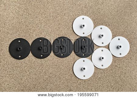 White and black round metal billets on the light tabletop. They are laid out in a form of the arrow. Closeup top view photo. Horizontal.