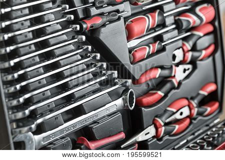 Closeup photo of the black toolbox. Inside it there are different sizes chrome spanners, black-red screwdrivers and pliers. Horizontal.