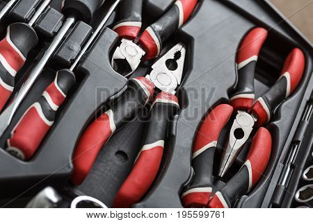 Black-red pliers and screwdrivers in the dark toolbox. Closeup top view photo. Horizontal.