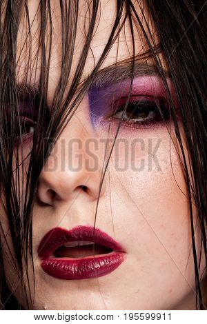 Sensual woman with artistic make up and wet hair in studio photo