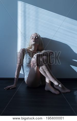 sad girl in linen sits on floor in moonlight with blinds toned image
