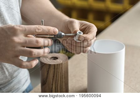 Constructor is using a t-wrench on the metal white detail in the workshop. On the table there are wooden and white metal cylindrical billets. Closeup. Horizontal.