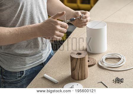 Specialist is using a t-wrench on the metal white detail in the workshop. On the table there are wooden and metal cylindrical billets, cable, connector and bushings. Closeup. Horizontal.