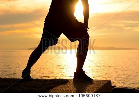 Silhouette of a man lower body stretching at the beaach in twilight