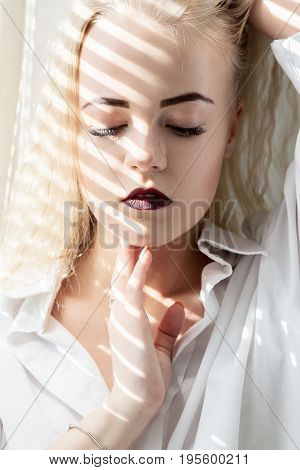 sad girl sitting on window in sunlight with blinds