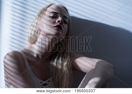 sad girl in linen sits in moonlight with blinds toned image