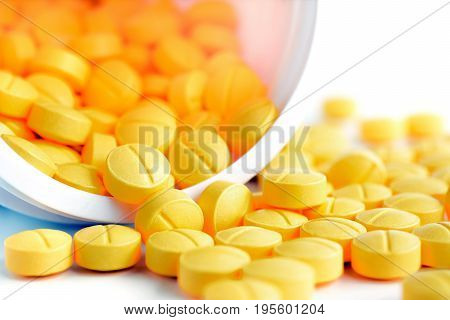 Small medicine tablets (or pills) spilling out from the bottle