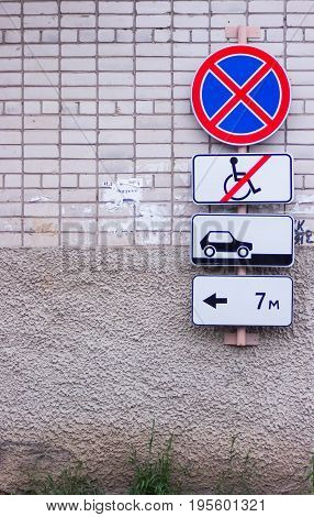 a couple of parking street signs on a brick wall in a russian city