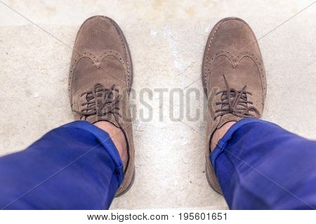 Young man wearing brown chamois shoes suite and blue pants. Businessman ready for a working day in office. Sitting hipster guy with old elegant shoes and typical turn-up jeans. Main focus on laces