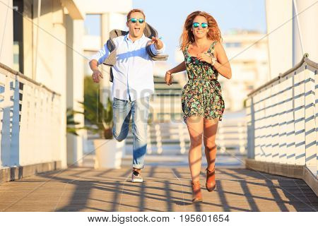 Young happy couple in love having fun and laughing together. Best friends enjoying beautiful sunset run near the beach. Girl run away from the guy. Funny - hilarious concept of partner in relationship