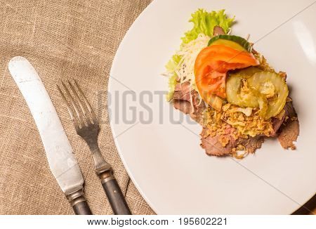Danish specialties and national dishes high-quality open sandwichRoast beef with remoulade and roasted crisp onions served on a plate ready for eating
