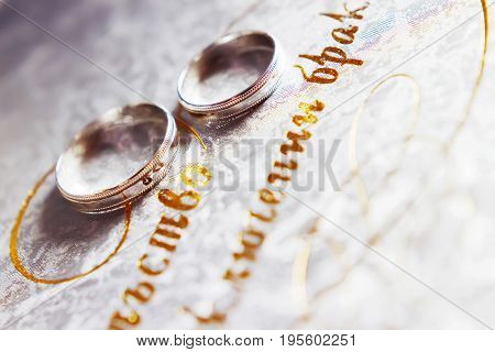 Pair of golden wedding rings on background with golden monogram. Symbol of love and marriage.