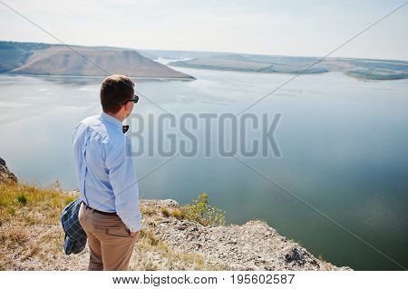 Lonely Groom Admiring Breathtaking View Of Lake Surrounded By Hills On His Wedding Day.
