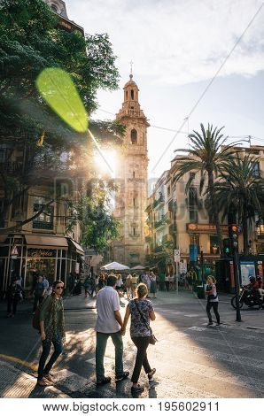 Valencia Spain - June 3 2017: Street view with Santa Caterina tower and passing tourists at sunset with bright sunlight plaza de la Reina Valencia Spain.